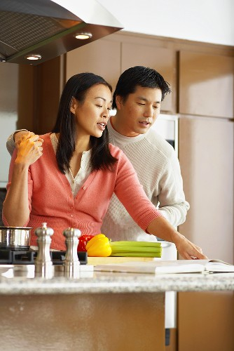 Young couple reading recipe from recipe book