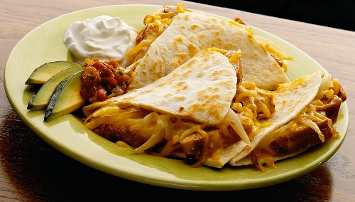 Cheesy Quesadilla on a Plate with Avocado Slices, Sour Cream and Salsa