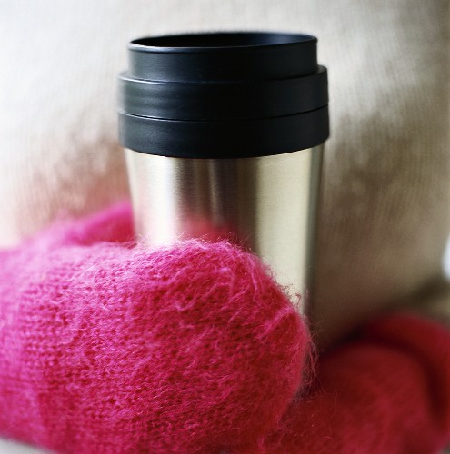 A Person with Fuzzy Pink Mittens Holding a Thermal Mug