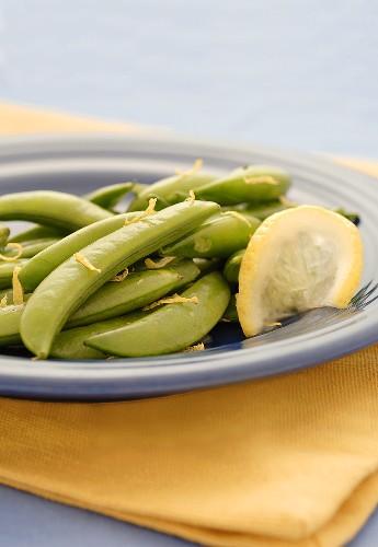 Sugar Snap Peas with Lemon Zest and Lemon Slice on Blue Plate