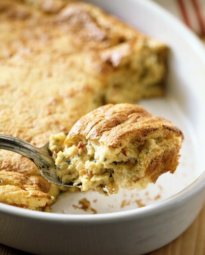 A spoonful of corn soufflé over baking dish