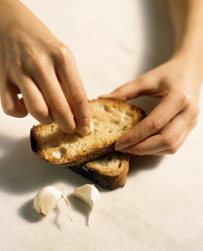 Rubbing garlic over slice of toasted bread