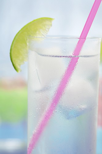 Glass of tonic water with ice cubes, lime and straw