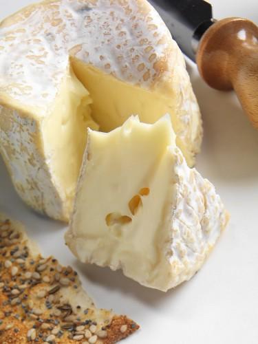 Petite Camembert, angeschnitten, mit Cracker und Käsemesser