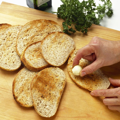 Hands Rubbing Garlic on Toasted Bread Slices