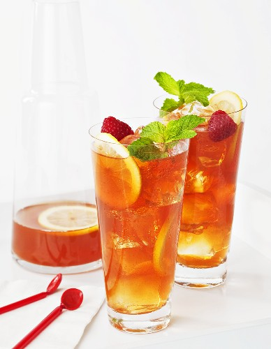 Two Glasses of Iced Tea with Raspberries and Lemon Slices