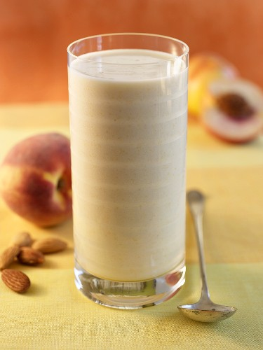 Peach Smoothie in a Glass; Spoon and Peaches