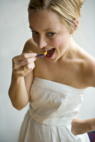 Woman in White Dress Eating Blue Corn Chip with Queso Dip