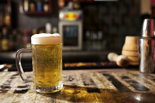 Glass of Beer with Foam on Bar Counter