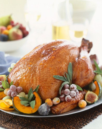 Whole Roasted Turkey on a Platter with Grapes, Figs and Sage