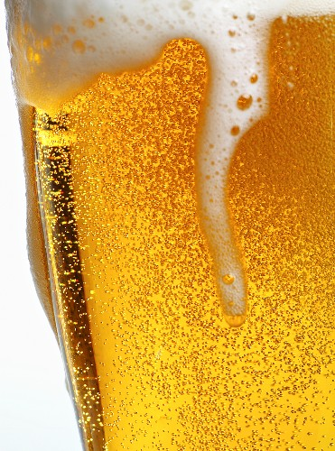 Foam Pouring Over Edge of Glass of Light Beer