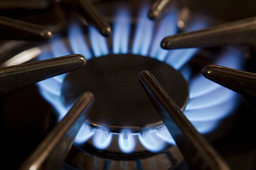 Thousand Oaks, California, USA. Domestic kitchen interior, Close up of the gas hob with the burner lit. Power heat and energy. Blue flames., Gas Burner on Stove