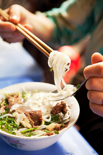 VIETNAM, Hanoi, restaurant Pho Gia Truyen, also known as 49 Bat Dan, a woman eats a bite of pho bo (beef noodle bowl) in the traditional way with a spoon and chopsticks