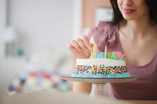 Mixed race woman preparing birthday cake, Jersey City, New Jersey, USA