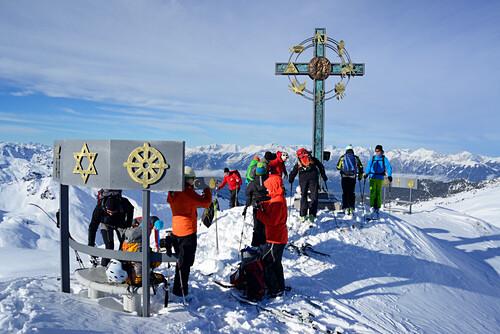 Skitourengeher an einem Gipfelkreuz mit … – Bild kaufen