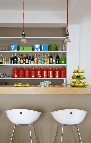 Breakfast at a bar - white stools in front of a bar and a shelf in the wall niche