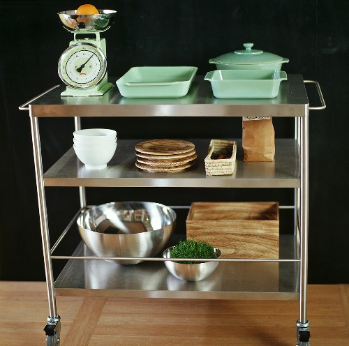 A tea trolley with stacked crockery and a pair of kitchen scales
