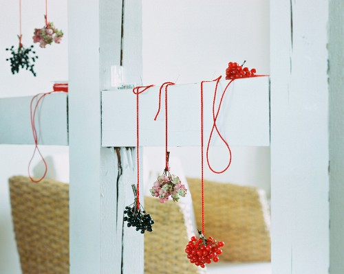 A small bouquet of berries hanging on a wooden beam
