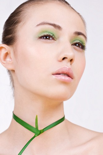 A young woman with green make-up with a plant around her neck