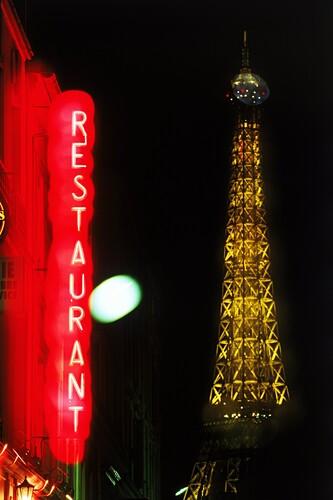 Schild eines Restaurants vor dem beleuchteten Eiffelturm, Paris, Frankreich, Europa
