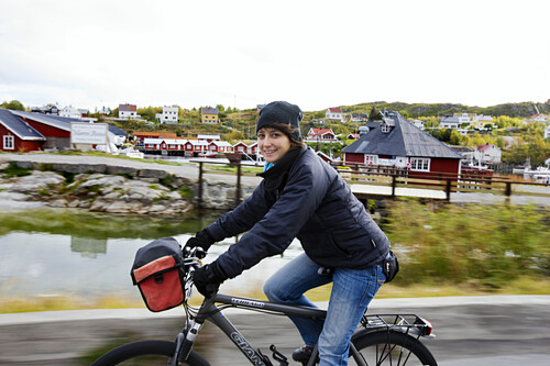 Young woman cycling and smiling in front of Reine, Lofoten, Norway, Scandinavia, Europe