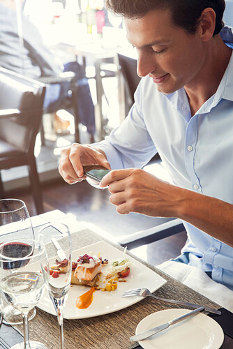 Man using smartphone to photograph his food in restaurant