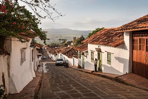 steile Gassen mit Blick auf das fruchtabre Umland und die Kathedrale, Barichara, Departmento Santander, Kolumbien, Südamerika