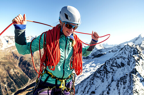 Young woman at the summit is picking up a rope at the summit of Gigalitz, Zillertal, Tyrol, Austria