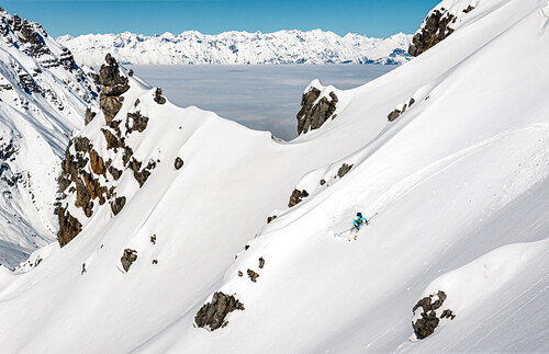 Young woman skies down an untracked slope with fresh powder, sea of clouds in the background, Stubai Alps, Tyrol, Austria