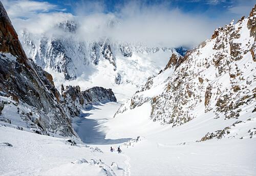 Two ski alpinists ascending towards the summit of Aiguille d'Argentière via the Glacier du Milieu, Chamonix, Haute-Savoie, France