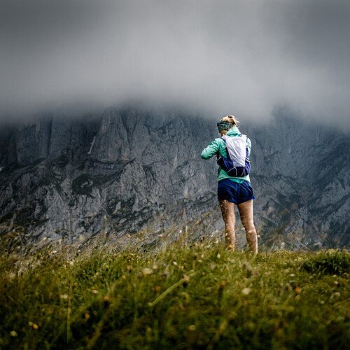 Young woman with running clothes is standing on a grassy hill in front of rock walls of Wilder Kaiser, stormy weather,Scheffau, Tyrol, Austria