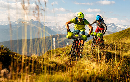Two middle aged mountainbikers are riding their bicycles on a singletrail through upgrown grass, mount Großvenediger in the background, Kirchberg, Tyrol, Austria