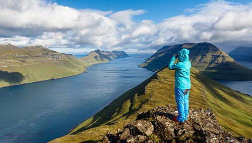 Young woman looks over the fjord landscape, the mountains and the ozean with a pair of binoculars on a bluebird day, Faroe Islands