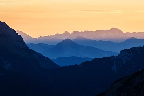 mountain silhouettes in yellow and blue tones, sunrise, Karwendel, Tyrol, Austria