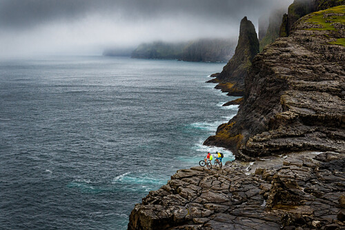 Two mountainbikers standing on a rock clif at the Atlantic Ocean, Faroe Islands