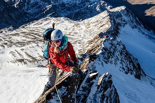 Young female mountaineer climbs on a ridge in the winter, Piz Tresero, Valfurva, Lombardia, South Tyrol, Italy