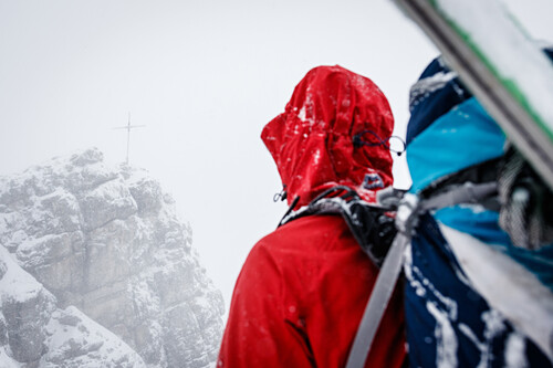 Young ski mountaineer has a look at the summit cross of mount Ponten, snowfall and mist, Allgäu, Germany