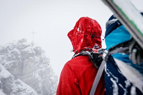 Junge Skialpinistin blickt auf das Gipfelkreuz des Ponten, Schneefall und Wolken, Allgäu, Deutschland