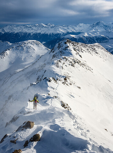 Young ski mountaineer travereses on a snowy ridge with skis on the backpack in windy conditions, Sesvenna, Vinschgau, South Tyrol, Italy