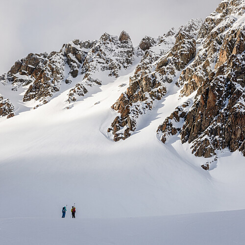 Two ski mountaineers have a look on an untracked, rocky slope, Tuoi hut, Scuol, Silvretta, Switzerland