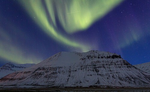 Polar lights over a snow covered mountain in the Westfjords, Iceland