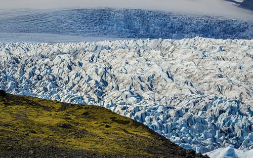 Grüner Hügel vor gigantischem Gletscherbruch, Jökulsárlón, Island