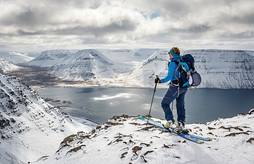 Skitourengeherin genießt die Aussicht vom Hólsfjall auf die Fjrodlandschaft der Westfjorde, Island