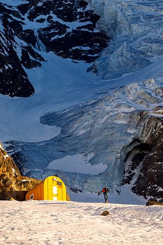 Skialpinistin im Aufstieg zum Günther Messer Biwak mit Gletscherabbruch des Hochferners im Hintergrund, Pfitschertal, Südtirol, Italien