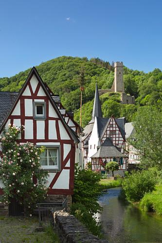 Blick über den Elzbach und die Fachwerkhäuser zur Phillipsburg, Monreal, Eifel, Rheinland-Pfalz, Deutschland