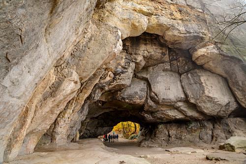 Gruppe Wanderer steht unter Felsbogen Kuhstall, Kuhstall, Kirnitzschtal, Elbsandsteingebirge, Nationalpark Sächsische Schweiz, Sächsische Schweiz, Sachsen, Deutschland