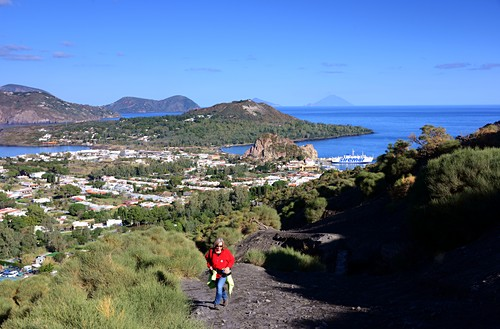 Woman on the way to the volcano with a view of Lipari, the sea and Stromboli, Vulkano Island, Aeolian Islands, southern Italy