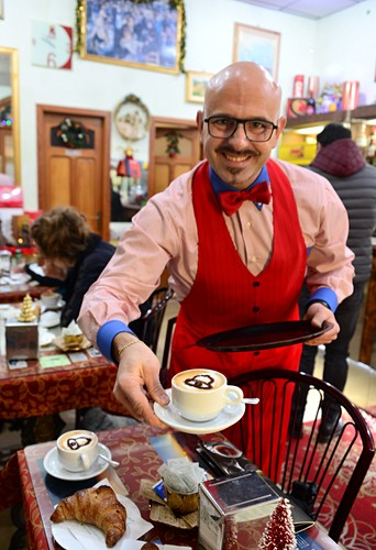 Ober serves two cappuchino, cafe in Sicily, Italy