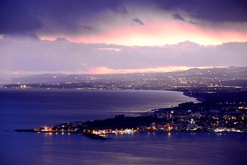 Evening view from Taormina to the south with sea and lights, east coast, Sicily, Italy