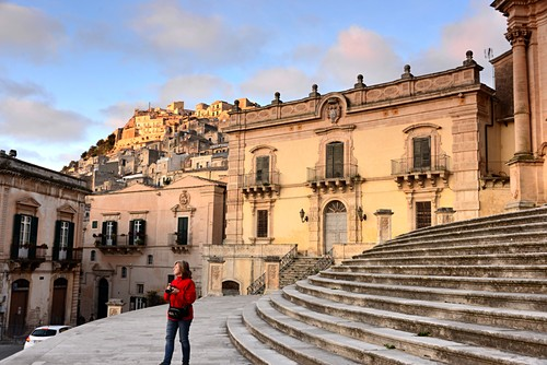 Palace, steps, woman at the Duomo, upper town of Modica, southern Sicily, Italy